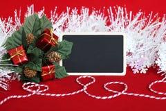 la pizarra en blanco rectangular para escribir un mensaje, hojas llenó de regalos rojos, de una guirnalda blanca helada y de un h Imágenes de archivo libres de regalías