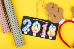 La pizarra en la cuerda con la inscripción 2018 hace de las velas, papel de embalaje, oídos de los ciervos del juguete en un docu Imagen de archivo libre de regalías