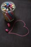 La pizarra, la tiza y el corazón forman vertical de dibujo Imagenes de archivo