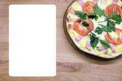 La pizza apetitosa con los tomates, el tocino y el queso en la placa redonda con la hoja blanca vacía para el menú mandan un SMS  Imagenes de archivo