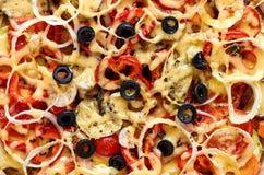 La pizza con i pomodori, il peperone dolce, la cipolla, le olive nere e le spezie strutturano il fondo Superficie di struttura de Fotografia Stock