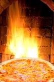 La pizza con il cotto di prosciutto di Parma ed il fuoco fiammeggiano in forno Fotografie Stock