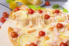La pizza con los pescados rojos de los mariscos, salmones, camarón, tomates, aún vida, queso, estiramientos, hombro, rebanada, su Imagen de archivo libre de regalías