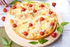 La pizza con los pescados rojos de los mariscos, salmones, camarón, tomates, aún vida, queso, estiramientos, hombro, rebanada, su Fotos de archivo