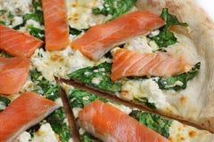 La pizza con la una pieza ascendente cercana de color salmón cortó fotografía de archivo
