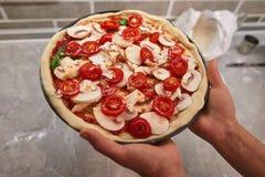 La pizza crue dans les mains d'un cuisinier est prête pour la cuisson photos stock