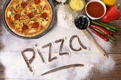 La pizza de la palabra escrita en harina con los diversos ingredientes Imágenes de archivo libres de regalías