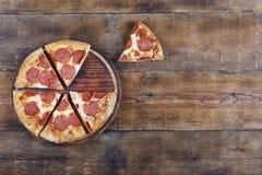 La pizza de Pepperone cortó en pedazos en un tablero de madera Imagen de archivo