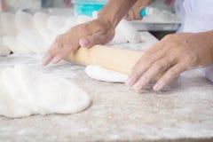 La pizza del cuoco unico passa la pasta di pane d'impastamento per pizza Immagini Stock