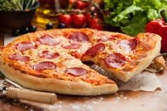 La pizza del salami levantó 1 rebanada Fotografía de archivo