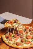 La pizza deliciosa sirvi? en la placa de madera - Imagen fotografía de archivo libre de regalías