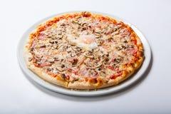 La pizza dell'Italia con il prosciutto del tuorlo d'uovo si espande rapidamente su un fondo bianco Fotografia Stock Libera da Diritti