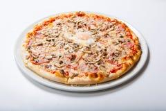 La pizza dell'Italia con il prosciutto del tuorlo d'uovo si espande rapidamente su un fondo bianco Fotografia Stock