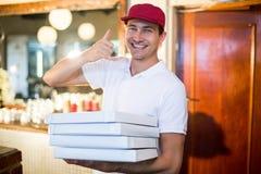 La pizza della tenuta del fattorino della pizza inscatola la fabbricazione del gesto del telefono Immagini Stock