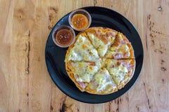 La pizza di formaggio e del bacon è servito in banda nera sulla tavola di legno immagine stock