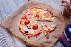 La pizza divertente del bambino ha cucinato in una classe di cottura, appena dal forno, alimento fresco caldo fotografia stock