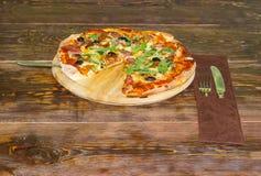 La pizza e la coltelleria cucinate hanno messo sulla vecchia tavola rustica immagini stock libere da diritti