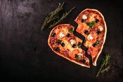 La pizza en forme de coeur avec des tomates et le mozzarella pour le jour de valentines sur le vintage noircissent le fond Concep Photographie stock libre de droits