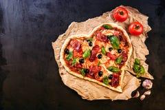 La pizza en forme de coeur avec des tomates et le mozzarella pour le jour de valentines sur le vintage noircissent le fond Concep Photos stock