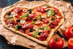 La pizza en forme de coeur avec des tomates et le prosciutto pour le jour de valentines sur le vintage noircissent le fond de tur Image stock