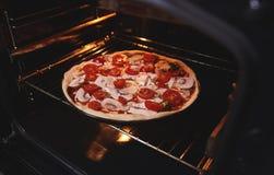 La pizza est à l'intérieur du four sur le gril de fer photo stock