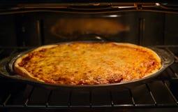La pizza fatta a mano sta cucinando in forno Formaggio al forno dell'oro come guarnizione fotografia stock libera da diritti