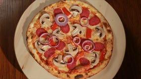 La pizza fraîchement cuite au four avec le salami, les champignons, l'oignon, et le poivre tourne autour Vue supérieure clips vidéos