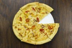 La pizza grande del corte con los tomates y el queso, con el pollo de la carne del jamón con la salsa verde que los alimentos de  Foto de archivo