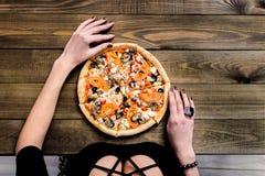 La pizza italienne COUPÉE EN TRANCHES TRÈS CHAUDE supérieure de vue de PLAN RAPPROCHÉ avec la main prennent une tranche sur la ta Image libre de droits