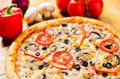 La pizza italienne délicieuse avec du maïs de fromage d'olives répand et des légumes Photographie stock