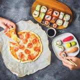 La pizza saporita con salame, l'insieme dei rotoli di sushi e le mani prendono l'alimento Fondo scuro Disposizione piana, vista s Fotografie Stock