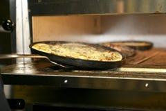 La pizza se está tomando de un horno Imagenes de archivo