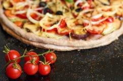 La pizza vegetariana calda con i pomodori, il peperone dolce, la cipolla, le olive nere, il formaggio, spezie su buio nero ha off Fotografie Stock Libere da Diritti