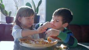 La pizzeria, amici allegri mangia l'alimento non sano durante il pranzo in caffè vicino alla finestra stock footage
