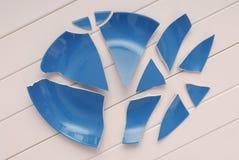La placa azul quebrada está en la tabla, plato descompuesto, tablewa machacado imagenes de archivo