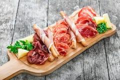 La placa con las barras de pan del grissini, prosciutto de la carne fría del disco del Antipasto, corta el jamón, cecina, salami  Imagen de archivo libre de regalías