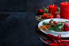 La placa con un árbol de navidad decorativo, a al lado de velas, una caja de regalo y cubiertos Fotografía de archivo