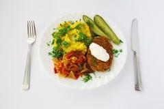 La placa de cena con la comida sirvió con el cuchillo y la fork Imágenes de archivo libres de regalías