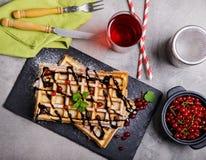 La placa de galletas belgas con la salsa de chocolate y la pasa dan fruto Foto de archivo