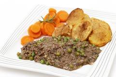 La placa de pica y los guisantes con las zanahorias y la patata Imagenes de archivo