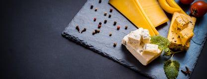La placa de queso con el queso verde, brie, queso duro de la trufa con las uvas, higos, peras, miel, galletas, secó las frutas y  fotografía de archivo libre de regalías