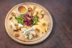 La placa de queso sirvió con las uvas, la miel y las nueces en un fondo de madera Imagen de archivo