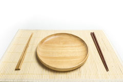 La placa o la bandeja de madera con el lugar de los palillos en una estera de bambú aisló el fondo blanco Foto de archivo
