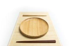 La placa o la bandeja de madera con el lugar de los palillos en una estera de bambú aisló el fondo blanco Imagenes de archivo