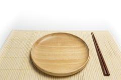 La placa o la bandeja de madera con el lugar de los palillos en una estera de bambú aisló el fondo blanco Fotografía de archivo