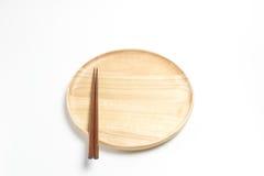 La placa o la bandeja de madera con los palillos aisló el fondo blanco Imagen de archivo