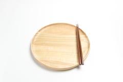 La placa o la bandeja de madera con los palillos aisló el fondo blanco Imagen de archivo libre de regalías