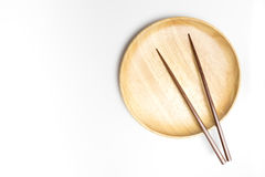 La placa o la bandeja de madera con los palillos aisló el fondo blanco Foto de archivo