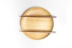 La placa o la bandeja de madera con los palillos aisló el fondo blanco Fotografía de archivo