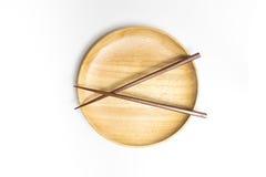 La placa o la bandeja de madera con los palillos aisló el fondo blanco Imágenes de archivo libres de regalías